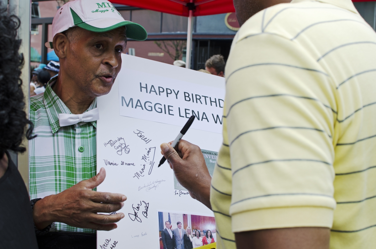 Community leader Melvin Jones passes around a birthday card for Maggie Walker at the unveiling of her monument. Photo by Haley Harrington, Oakwood Arts.