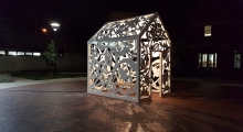 A nighttime photo of a public art sculpture in the shape of a small house covered in decorative cut-out shapes. A light from inside casts shadows of the shapes around the sculpture.