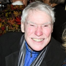 A smiling man with white hair wearing a black suit coat.