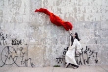 A dancer dressed in white waves a large red cloth in the air in front of a concrete wall adorned with spray painted graffiti written in Japanese characters.