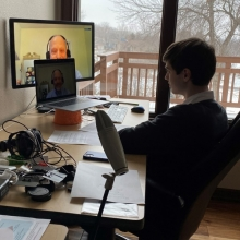 Sean Baker, a high school student, sits in front of two computer screens conducting a video interview with Randy Cohen of Americans for the Arts.